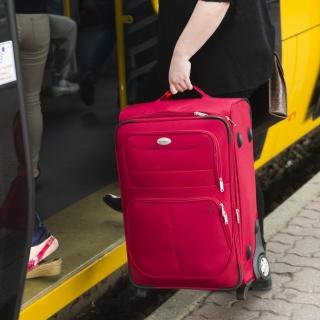 kobieta wnosząca walizkę podróżną do tramwaju