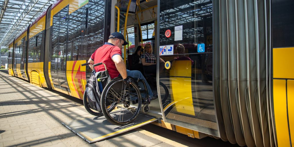 a wheelchair user enters a tram on a ramp in the second door