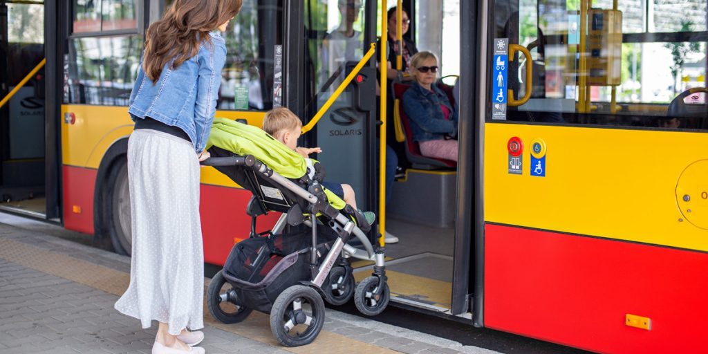 a person with a pram gets on the bus through the second door