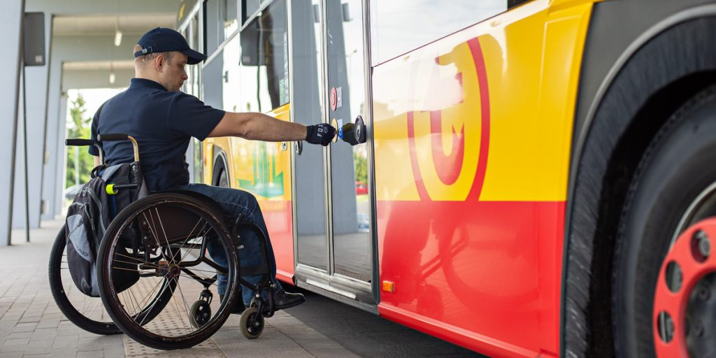 a wheelchair user presses the blue button next to the second door to inform the driver about the need to unfold the ramp