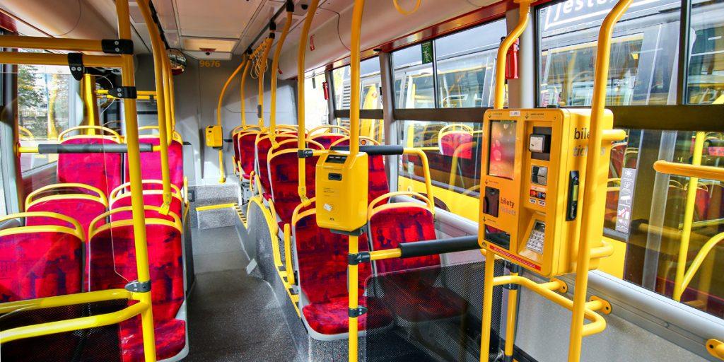 wnętrze autobusu, w którym widać kasowniki oraz automat biletowy