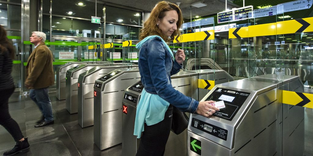 A woman puts the Warsaw City Card against the subway gate to enter the ticket zone.