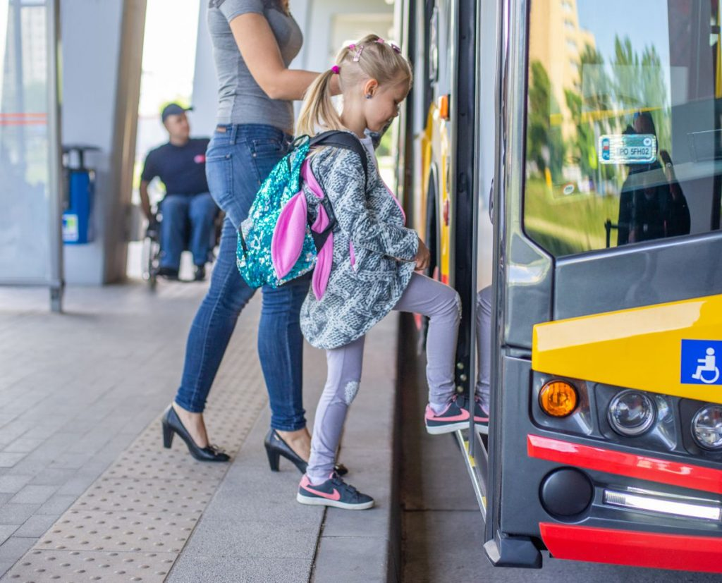 zdjęcie przestawiające dziewczynkę z tornistrem wchodzącą do autobusu WTP